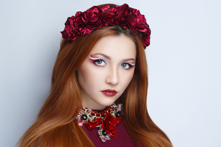 Bright orange brown long straight hair. Oriental beauty girl professional makeup. Portrait of a beautiful woman who wore big flower wreath accessory. Young gypsy fortune teller predicts fate horoscope Banco de Imagens