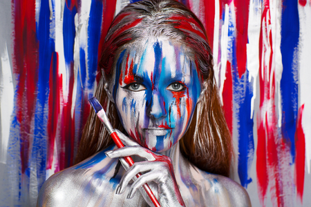Girl painter with big artist professional red brush, all body Painted in gouache watercolor acrylic oil paints. Creative makeup new conceptual idea. Crazy new graphic abstract picture woman face lines Stock Photo