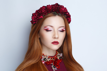 Bright orange brown long straight hair. Oriental beauty girl professional makeup. Portrait of a beautiful woman who wore big flower wreath accessory. Young gypsy fortune teller predicts fate horoscope Stock Photo