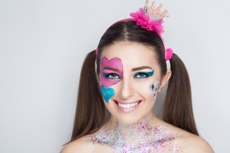 Beautiful magical charming woman, love princess with big and small painted hearts on face. hair tails. Figure paint her cheek blush, bright shadows eye makeup glossy shiny lipstick. accessory jewelry