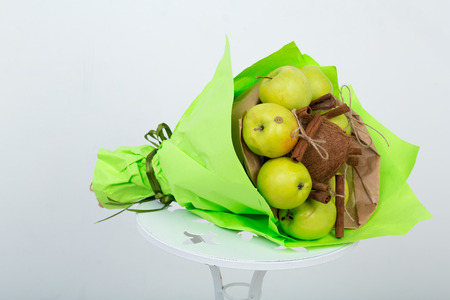 Bouquet made of fruits. original unusual edible present. Close up. useful gift for a proper lifestyle. autumn harvesting of fresh apples, coconut, cinnamon concept of accumulate vitamins for winter