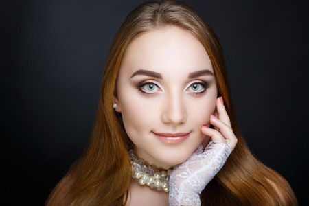 Beautiful woman white accessory lace gloves, long clean combed hair. Professional cosmetics nude makeup. Shiny beige lip-gloss lipstick. New photo closeup portrait, black color background horizontal
