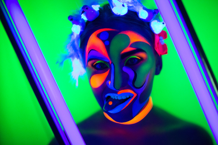Creative woman lady girl model shine with blue green orange colors. New Bright conceptual art make-up glows under ultraviolet light. Club disco neon party time. Drink alcohol feel wild energy of music