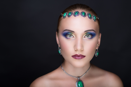 Young beautiful woman Professional bright blue make up close-up eyelids. tiara ring made of beads natural stones emerald virid green. Conceptual horizontal photo free place for text. Necked sexy body