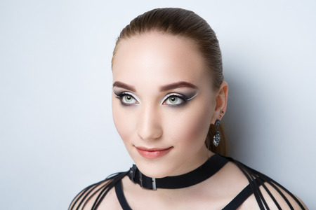 Beautiful woman, necklace choker leather belt. Professional cosmetics intensive makeup. Beige matte lips lipstick lipgloss, shiny shadows. New photo close up portrait, gray color background horizontal