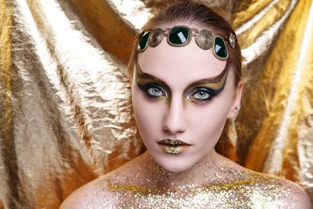 巨大なティアラの王冠を身に着けている美しい女性。髪がきつく縛られている。プロの化粧品のメイクアップ。キラキラ口紅のリップグロス。新し