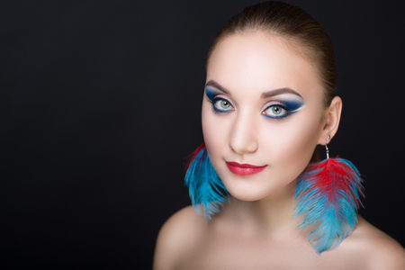 Circus Girl feathers, Close-up portrait of perfect woman faceart. Bright make up red lips, blue shadows. tightly tied hair, birds ultramarine feather earrings. New art creative idea. Horizontal banner Stock Photo