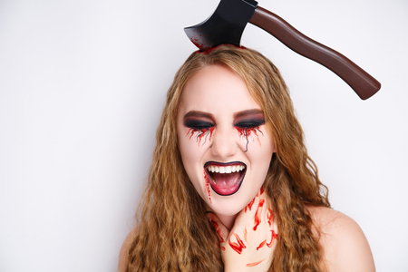 Beautiful girl with big massive ax in her head. Creative make-up conceptual crazy idea for Halloween night party. Nightmare carnival costume, body art painting. Professional close photo. skin injured Stock Photo