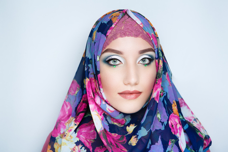 Young beautiful woman (lady girl) in a headscarf hijab. Professional cosmetics bright makeup. Shiny lipstick lip-gloss, new shadows. New photo closeup portrait, gray color background horizontal banner