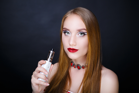 Young beautiful woman girl lady smokes electronic cigarette. model fashionable hairdo, professional makeup red color trendy lips lip-gloss. Closeup horizontal photo face. black background free place
