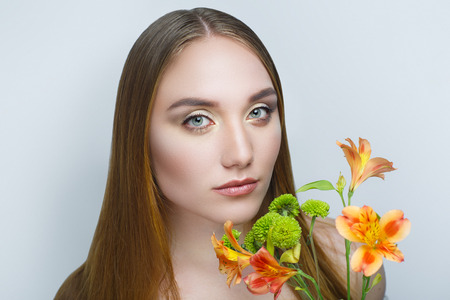Beautiful woman with orange flowers, long clean combed hair, necked shoulders. Professional cosmetics nude makeup. Beige shiny lipstick. New photo close up portrait, gray color background horizontal Stock Photo