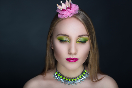 Circus Girl Princess Frog, Close-up portrait of perfect woman faceart. Bright make up pink lips, green shadows. light Golden hair, luxury accessory necklace. New art creative idea. Horizontal banner  Stock Photo