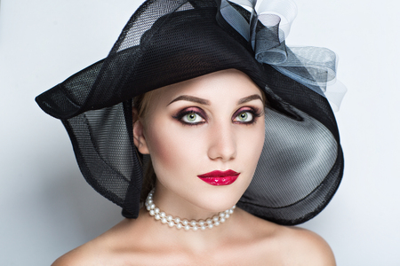 Closeup portrait of beautiful girl woman lady with make up studio styling. Luxury makeup Bright black purple shiny red lipstick, big hat. Professional photo exclusive model vip person, gray background Stock Photo