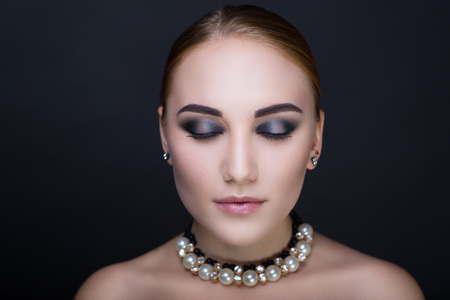 Young beautiful girl with a fashionable hairdo and professional makeup. Black gray eye shadows, perfect shape of brows, tender shiny pink lips color lipstick. Luxury accessory necklace with big pearls Stock Photo