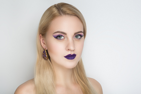 Closeup portrait of beautiful girl woman lady with volume combed hair styling. Luxury blonde gray white silver combed hair. Bright violet makeup, shiny lipstick. Professional photo model vip person