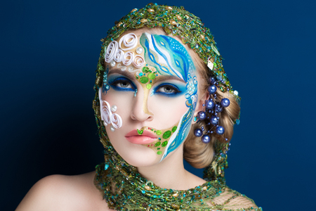 Creative make-up new conceptual idea. colorful bold faceart body art painting accessory. new graphic abstract picture woman face surrealistic. professional photo. Creativity lines concept composition