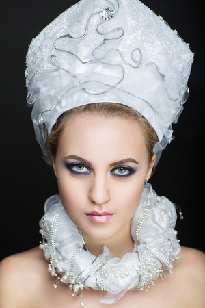 Young face close up photo portrait. Beautiful girl wearing Christmas suit Snow Maiden frozen crown. Pretty woman emotions, prepare for New Year party. Santa girl dreaming about presents and surprises