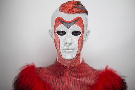White & red man from Outer Space, Alien. Black eyes, white skin, red cheekbones, neck, ears Face art, decoration, geometry, cubism, full fashion look. Creative make up made by professional cosmetics.