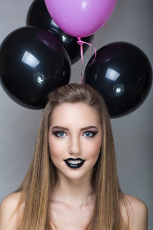New Mini mouse style, big black balloons, sexy lips lipgloss. Blond beautiful beauty girl professional makeup pretty face, long light blond combed hair. Grey background. Necked erotic body shoulders
