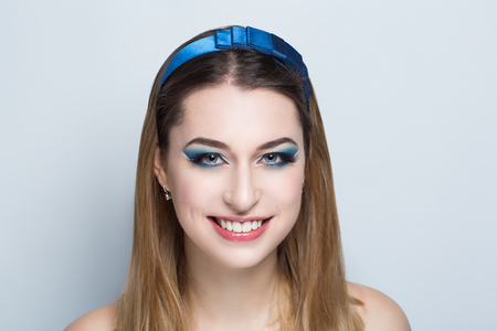 Closeup portrait of beautiful girl woman lady with combed hair styling. Luxury blue tiara diadem hoop jewelry. Bright shadows makeup, shiny pink lipstick lip gloss. Professional photo model vip person