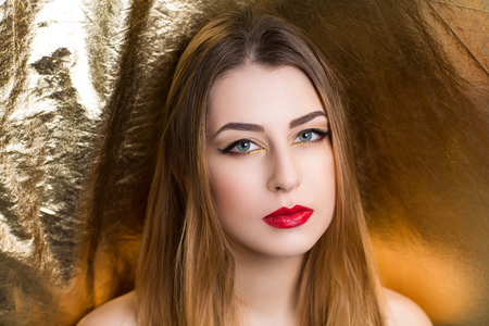 Creative golden girl bright makeup blond hair. Streams gold shiny cheek colored face, matte red lips luxury body art. Sexy naked shoulders. Professional photo, new stylish idea. giant sheet of foil Stock Photo