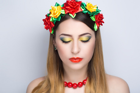 Beautiful woman with yellow red flowers accessory, long clean combed hair, necked shoulders. Professional cosmetics makeup. Shiny lipstick. New photo closeup portrait, gray color background horizontal
