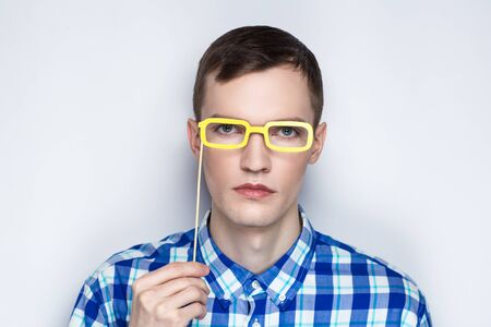 Paper eyeglasses hand made crafts, accessories cardboard attributes on sticks for a professional photo shoot. Young man holding object in his arm. Expressing emotions of serious person love studying Stock Photo