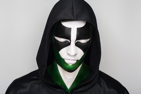Creative man boy model black white green colors. Bright conceptual art makeup glows light party time. Multicolored clamps, clips dark hood covered had. Artistic shiny comics lifestyle. Strange emotion