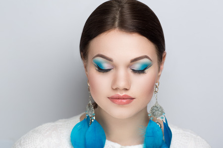 Circus Girl feathers, Close-up portrait of perfect woman faceart. Bright make up beige lips, blue shadows. Brunette hair, birds ultramarine feather earrings. New art creative idea. Horizontal banner