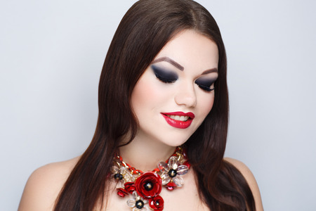 Beautiful woman with necklace choker red flowers. Long straight hair brunette. Professional cosmetics makeup. Red matt lipstick lip-gloss. New photo close up portrait, gray color background horizontal Banque d'images