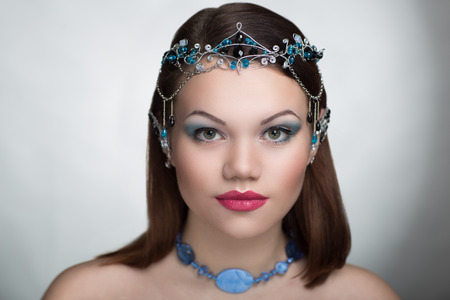 Young beautiful woman Professional bright pink make up close-up eyelids. Short cut combed clean healthy hair tiara ring made of beads. Conceptual horizontal photo free place for text. Necked sexy body