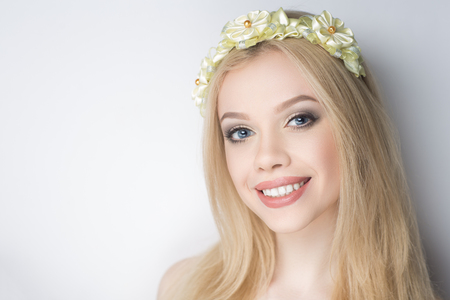Young beautiful woman girl lady with ivory flowers wreath on her head. model fashionable hairdo professional makeup gold color trendy shadows. Closeup horizontal photo face. gray background free place