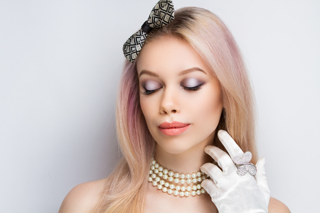 Retro vintage style, gloves white satin fabric, luxurious decoration on sexy neck old-fashioned pearl necklace. New professional make up beige lips, golden color hair-do, arrows shadows decorates eyes 免版税图像