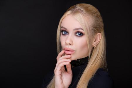 Beautiful woman, fingers touch face. Professional cosmetics intensive makeup, manicure. Beige matte lips lipstick lip-gloss, shiny shadows. New photo close portrait, black color background horizontal Reklamní fotografie