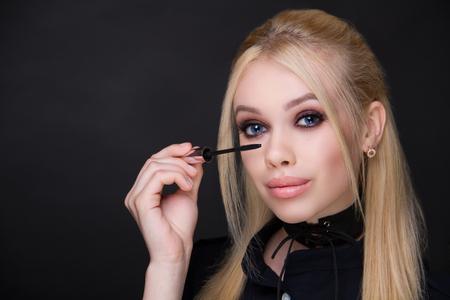Beautiful woman, mascara brush eyes. Professional cosmetics intensive makeup smoky eyes. Beige matte lips lipstick lip-gloss, shiny shadows. Photo close-up portrait, black color background horizontal Stock Photo