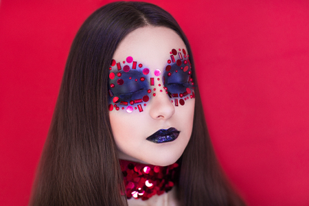 Red passion woman closeup portrait. beads and sequins fabric luxury material. Conceptual idea make up studio shaggy overgrown eyebrows brow master. Expensive cosmetics marsala color lipstick long hair Stockfoto