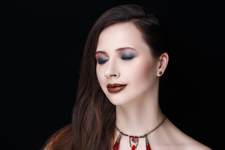 Beautiful woman with red jewels, long brunette hair styling, necked shoulders. Professional cosmetics makeup. Brown shiny lipstick. New photo close up portrait, black color background horizontal Stock Photo