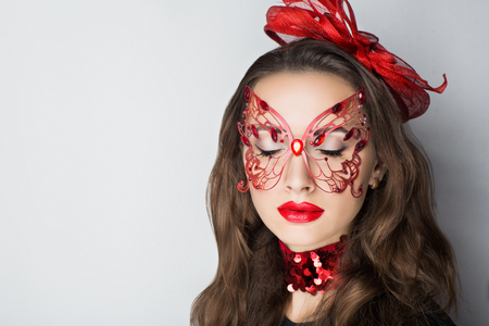 Beauty portrait of a beautiful young woman girl lady model, red lips, openwork butterfly paper. Professional makeup studio. big carnival mask prepare for party masquerade in Brazil Italy Venice France