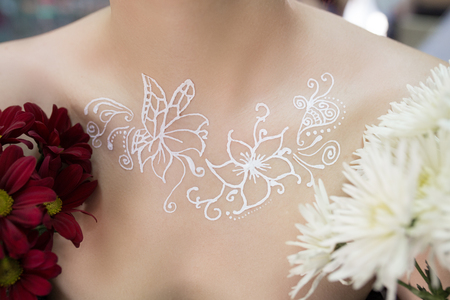 Drawing mehendi on white skin woman chest, decolletage idea. Picture abstract flowers butterfly. Henna painting design wedding party. branches of lilac. Close up professional photo horizontal banner Stock Photo
