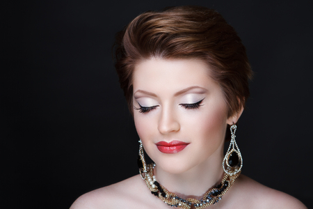 Beautiful woman with gold jewels, short haircut brunette, necked shoulders. Professional cosmetics makeup. Red shiny lipstick. New photo close up portrait, black color background horizontal Stock Photo