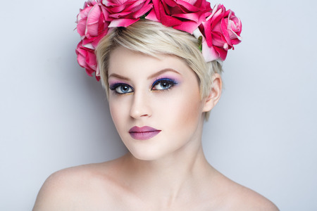 Closeup portrait of beautiful girl woman lady with short haircut hair styling. Luxury Bright makeup shiny lipstick cosmetics. New Professional photo model vip person, big flower accessory wreath roses Stock Photo
