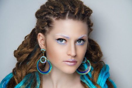Young beautiful girl with brown and blue dreadlocks. Stylish volume hair-do, professional make-up art, gray white brows albino skin. Large round earrings, massive jewelry accessory. Afro weave braids.
