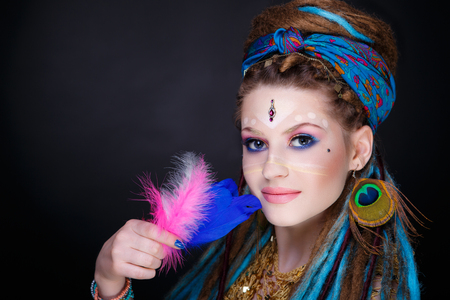 Young beautiful girl woman with brown, blue dreadlocks. Stylish volume hair-do, professional make-up art, white picture. Large peacock feathers earrings, massive jewelry accessory. Afro weave braids Standard-Bild