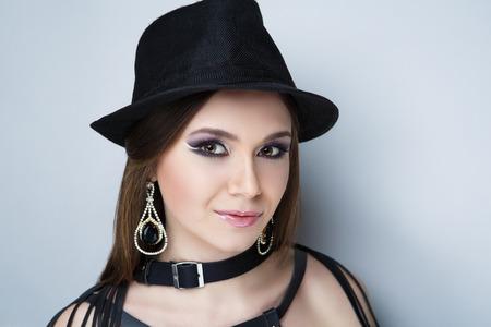 Beautiful woman, necklace choker leather belt, stylish hat. Long hair. Professional cosmetics makeup. Beige pink matte lipstick lip-gloss. New photo close portrait, gray color background horizontal
