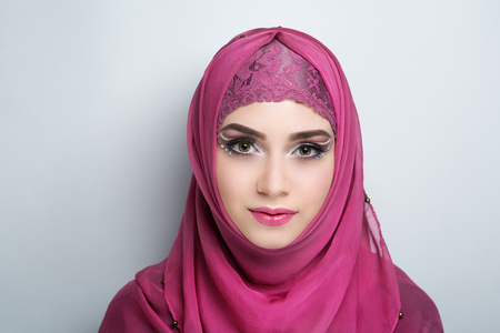 Young beautiful woman (lady girl) headscarf hijab. Professional cosmetics bright makeup. Shiny pink lips lipstick lipgloss, shadows. New photo closeup portrait, gray color background horizontal banner