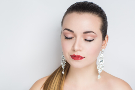 Beautiful bride woman girl lady princess prepare for wedding party, long silver swarovski crystals diamond earrings. Professional make up bright eyes, red shiny lips lipstick. gray background clipping