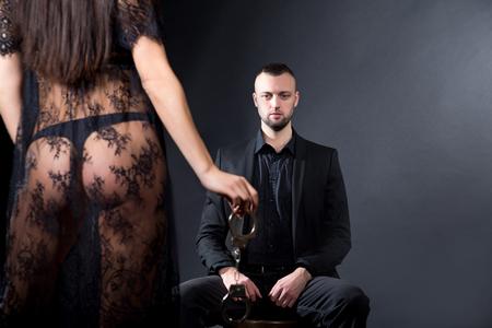 Les amoureux, homme et femme, se préparent aux jeux de rôle. Dominer obéir se déshabiller séduit un partenaire. Fille vêtue d'un négligé en dentelle noire, vêtue de sous-vêtements sexy. Une idée de date sensuelle. Soirée thématique bdsm
