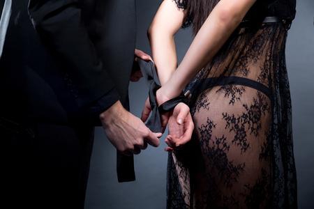 Amantes homem e mulher estão se preparando para role-playing games. Domine obedecer despir seduzir um parceiro. Menina vestida de lingerie preta rendada, vestindo lingerie sexy. Uma ideia de encontro sensual. Festa de bdsm temática Foto de archivo - 94797719