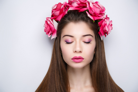 Beautiful woman wearing massive flower wreath. Long black straight hair. Professional cosmetics makeup. Natural lipstick lip-gloss. New photo close up portrait, gray color background horizontal banner Banque d'images - 94881865