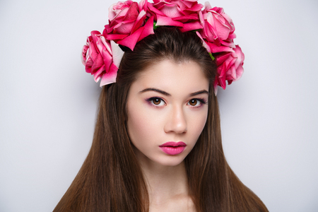 Beautiful woman wearing massive flower wreath. Long black straight hair. Professional cosmetics makeup. Natural lipstick lip-gloss. New photo close up portrait, gray color background horizontal banner Banque d'images - 94881887